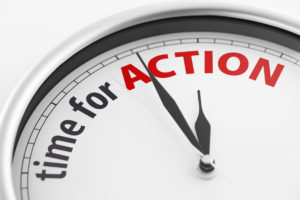 """Close-up of a clock showing the words """"Time For Action"""". Shallow depth of field."""